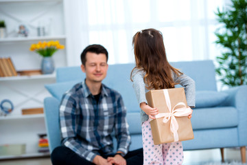 Cute little girl, daughter, sister gives a gift box to young dad father or brother. Both are smiling. Father's day holiday concept, Children's Day