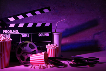 Movie clapper with film reel and popcorn on table