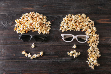 Funny couple made of popcorn on dark wooden background