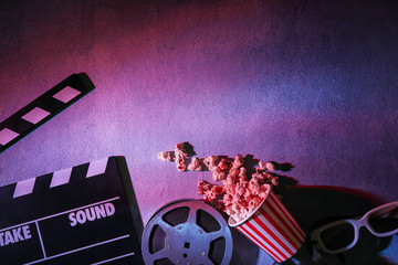 Movie clapper, film reel with popcorn and glasses on grey background