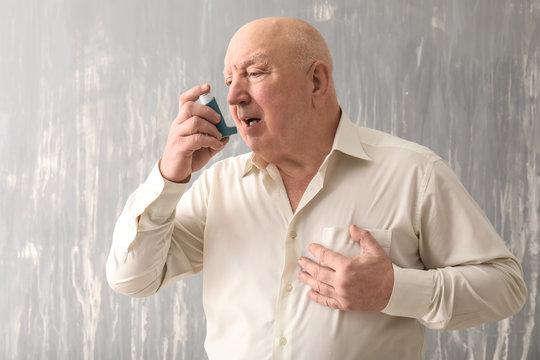 Senior man with inhaler having asthma attack on grey background