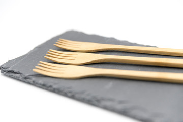 Wooden fork on slate plate on white background