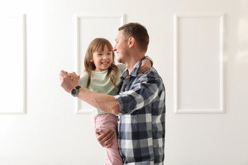 Father and his cute little daughter dancing at home