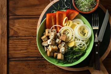 Tasty salad with tofu cheese on wooden table