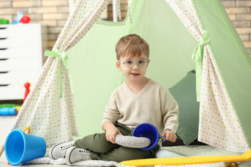 Portrait of cute little boy sitting in hovel at home Wall mural