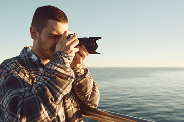 un chico joven utiliza una cámara sin espejo en un atardecer en Badalona, Barcelona