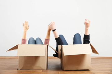 cheerful couple lying in boxes