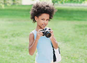 Happy smiling little girl with a digital camera. Beautiful kid girl portrait.  Isolated on gray background. Summer fun, vacations concept