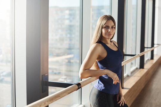 Sport, recreation, wellness concept. Determined fit confident female fitness instructor in activewear leaning on ballet barre near window smiling assured, pilates instuctor waiting for trainees