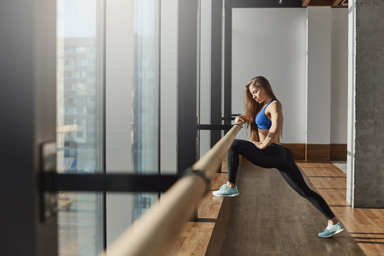 Young motivated determined woman in sportswear sports-bra leggings stretching legs on ballet barre standing near gym window focused exercising, preparing muscles working-out accomplish 2019 goals