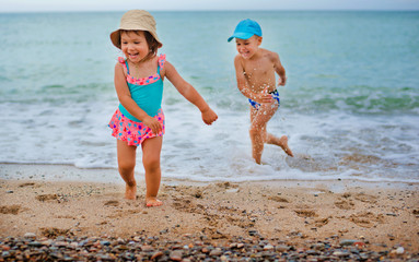 Boy and girl playing on the beach on summer holidays.