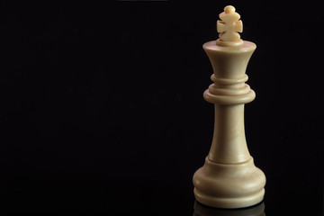 Classic Chess White King on black surface, isolated