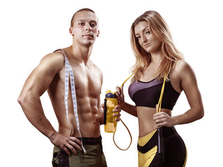 Athletic couple isolated over white background. Muscular Man and Woman with measuring tape in gym. Weight loss, bodybuilding, sport and fitness, coach, workout, dieting and health. - Image