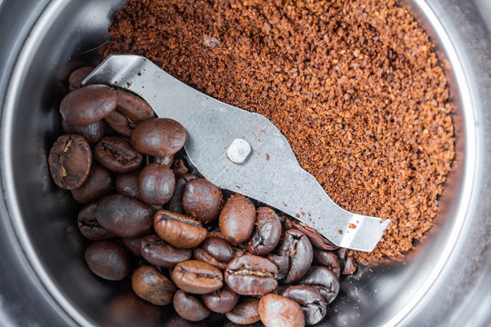 A metal electric coffee grinder. One side of coffee grinder with whole grains of coffee, another with ground. Closeup, selective focus, top view