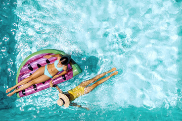 People relaxing on inflatable lilo in hotel pool