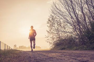 Wall Mural - Uomo che corre su strada di campagna all'alba