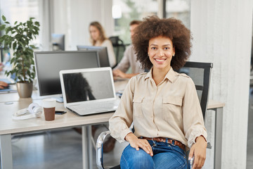 Smiling mixed race CEO sitting at office and looking at camera. In background employees working.