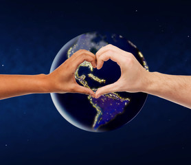 love, diversity and charity concept - mixed-race couple hands showing heart gesture over earth planet in space