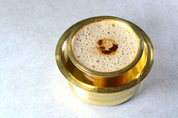 Indian Filter Coffee served in brass cup and saucer.