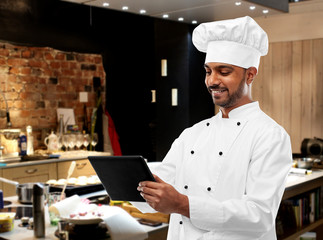 cooking, profession and people concept - happy male indian chef in toque with clipboard over black chalkboard background