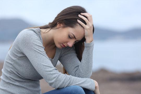 Sad woman on the beach complaining alone