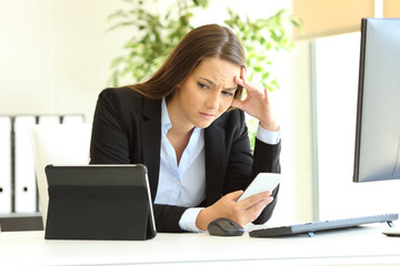 Worried office worker using multiple devices