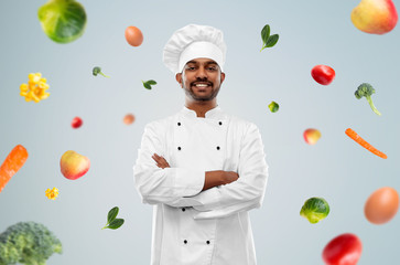 cooking, profession and healthy eating concept - happy male indian chef in toque over blue background and vegetables