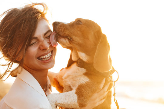 Image of happy woman 20s hugging her dog, while sitting on sand by seaside