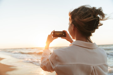Image of attractive woman 20s taking photo on smartphone, while walking by seaside