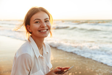 Image of happy woman 20s smiling and using cell phone, while walking by seaside