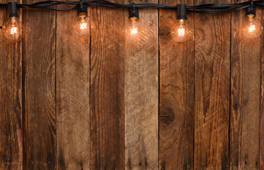 Vintage garland string lights on old wooden wall border with copy space
