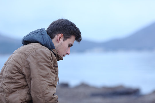 Sad man in winter on the beach complaining