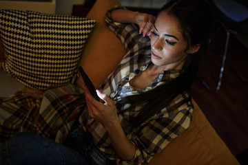 Attractive woman sitting at home on pleasant evening and chatting with friends on smart phone.