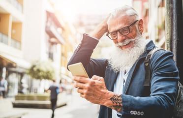 Trendy senior man using smartphone app in downtowgn center outdoor Fotoväggar