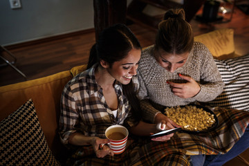 Two female best friends sitting at home on pleasant evening and spending time on social network via smart phone.