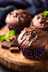 Chocolate cakes decorated with chocolate and mint leaf on wooden serving board. Closeup view. Tasty chocolate muffins or cupcakes