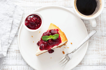 Slice of cheesecake with berry sauce and cup of coffee on white wooden table background. Table top view. Breakfast, coffee time in cafe