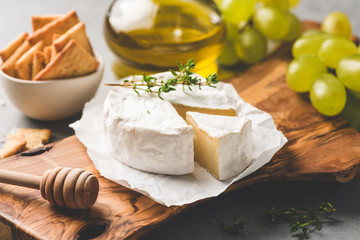 Brie or camembert cheese, crackers, honey, grapes on wooden serving board. Cheese board