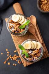 Granola Banana Breakfast in Jar on wooden serving board, top view