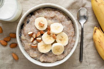 Oatmeal porridge with banana and nuts, top view. Vegan, vegetarian breakfast meal, healthy eating concept