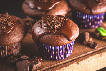 Chocolate muffins with ganache on a wooden serving tray. Closeup view of tasty chocolate cakes. Toned image.