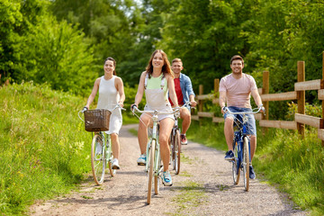 people, leisure and lifestyle concept - happy young friends riding fixed gear bicycles on country road in summer Wall mural