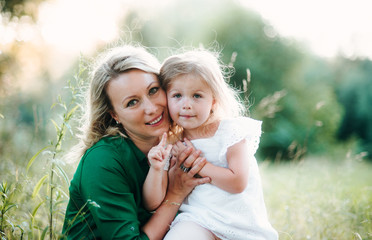 A portrait of young mother in nature with small daughter in summer.