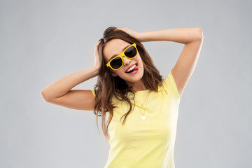 summer, accessory and people concept - smiling young woman or teenage girl in yellow t-shirt and sunglasses holding to her head over grey background