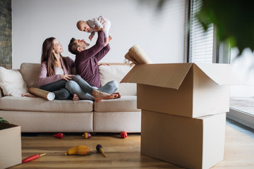 Fototapeta A portrait of young couple with a baby and cardboard boxes moving in a new home. obraz