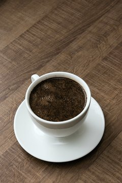 preparing hot coffee into a white mug