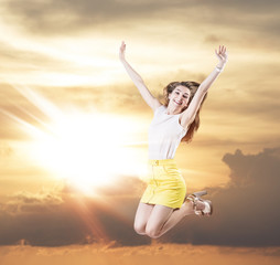 Young woman jumps in the cloudy sky.