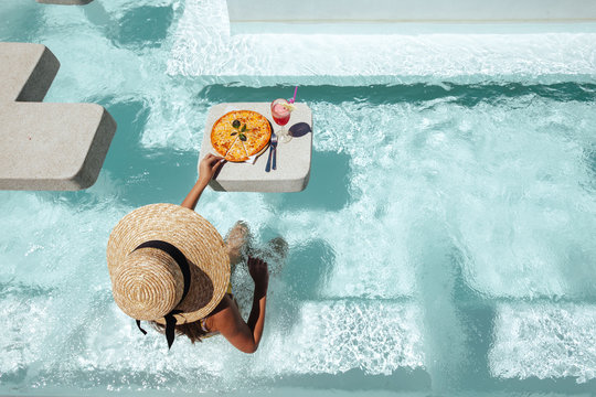 Girl eating pizza in pool