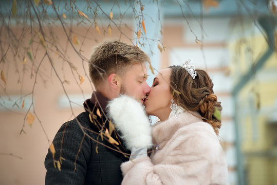 Bride and groom kiss on a winter day close-up. Wedding couple on the street.