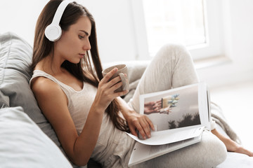 Young woman sitting on sofa indoors at home listening music with headphones drinking tea reading magazine.